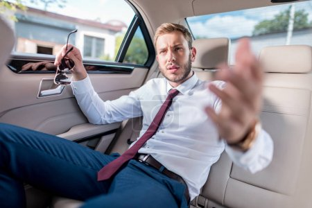 Businessman on backseat of car