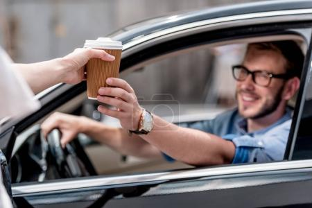 Man with coffee in car