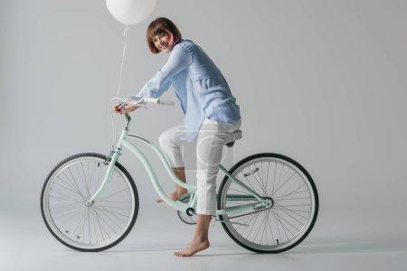 girl on bike with balloon