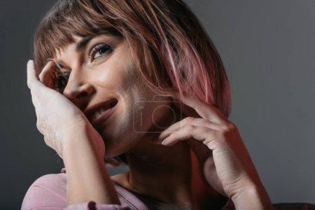 Photo pour Heureuse jolie fille avec de la poudre sur le visage et les mains, isolé sur gris - image libre de droit