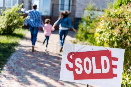 Photo for Family running to new house with sold signboard on foreground - Royalty Free Image