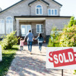 Family moving into new house with sold signboard o...