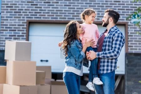 Foto de Familia joven frente a casa de nuevo con muchas cajas de pie camino al garaje - Imagen libre de derechos