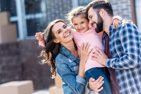 Photo for Happy young family embracing in front of new house - Royalty Free Image