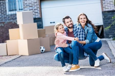 family sitting in front of new house