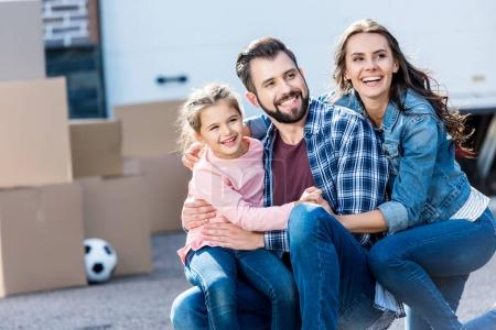 Photo for Happy young family sitting in front of new house - Royalty Free Image