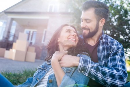 Photo for Couple relaxing on grass in front of new house - Royalty Free Image