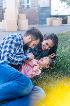 parents cuddling daughter on grass