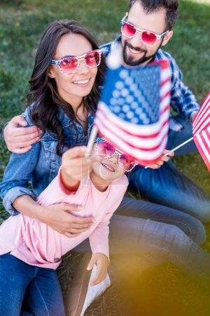 Photo for Beautiful  american family sitting on grass with usa flags and sunglasses - Royalty Free Image
