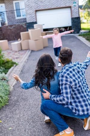 Photo pour Heureuse belle fille courir pour embrasser des parents - image libre de droit