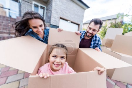 Girl sitting in cardboard box