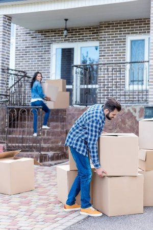Photo for Young couple with cardboard boxes moving into new house - Royalty Free Image