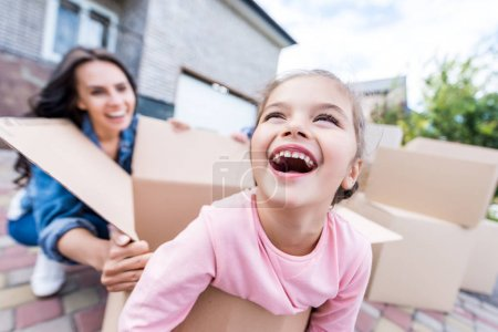 Mother and daughter having fun with boxes