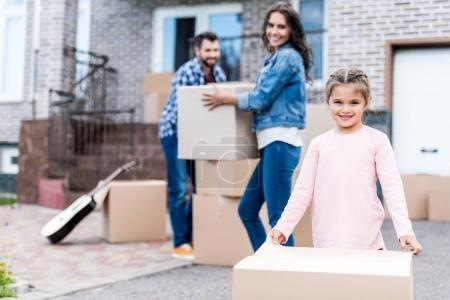 Photo for Young family carrying boxes for moving into new home - Royalty Free Image