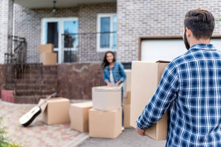 Photo for Couple with cardboard boxes moving into new house - Royalty Free Image