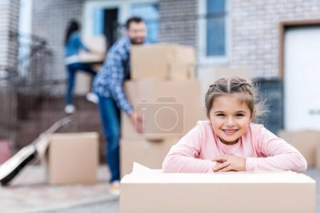 Photo for Adorable little girl with cardboard box with parents moving into new home on background - Royalty Free Image