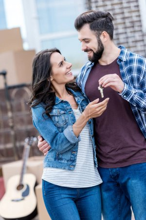 Photo for Beautiful couple with keys in front of new house - Royalty Free Image