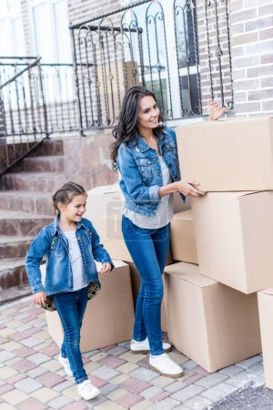 Photo for Beautiful mother and daughter with cardboard boxes next to new house - Royalty Free Image