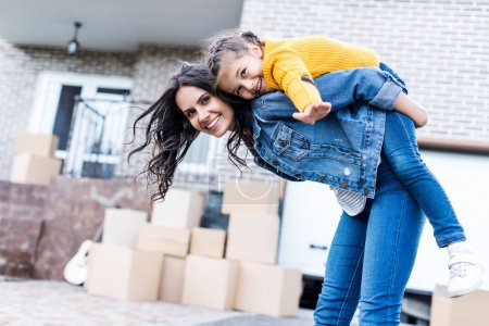 Photo for Happy daughter piggyback riding mother in front of new house - Royalty Free Image
