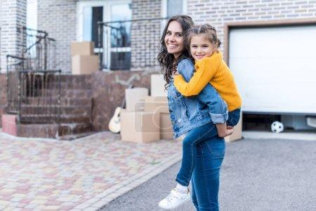 daughter piggyback riding mother
