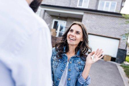 Photo pour Surpris de jeune femme regardant l'homme avec des clés en main - image libre de droit