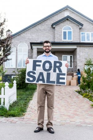 realtor with banner for sale