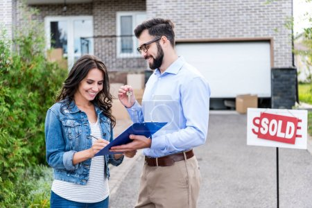 Woman signing contract with realtor