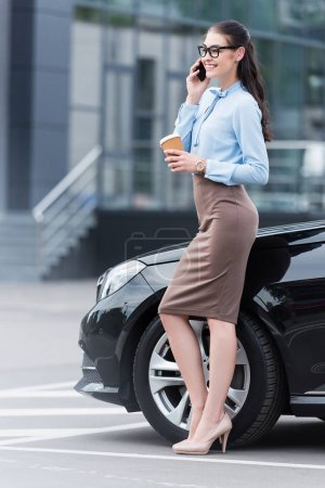 businesswoman talking on smartphone with coffee
