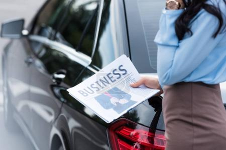 Woman holding business newspaper