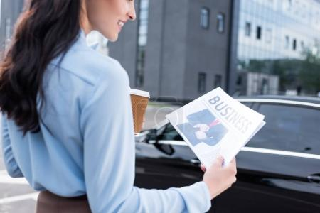 Woman holding business newspaper and coffee