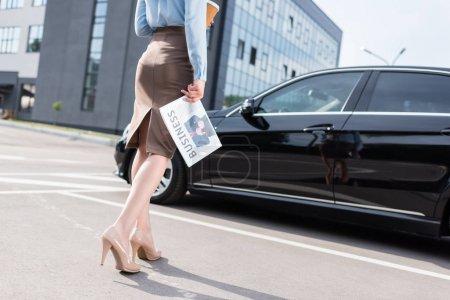 Businesswoman holding business newspaper