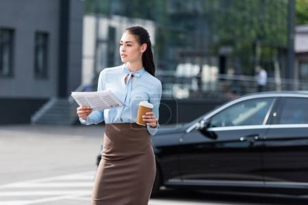 Businesswoman holding business newspaper and coffee