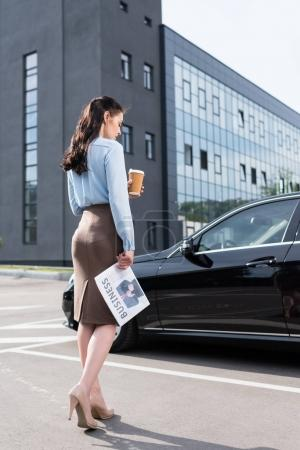 Businesswoman holding newspaper and coffee