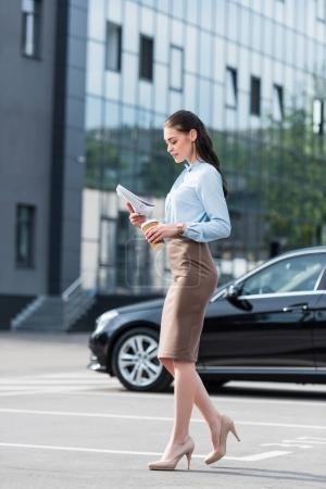 Businesswoman reading business newspaper