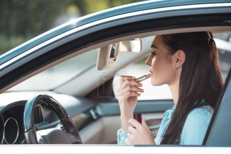woman applying lipstick in car