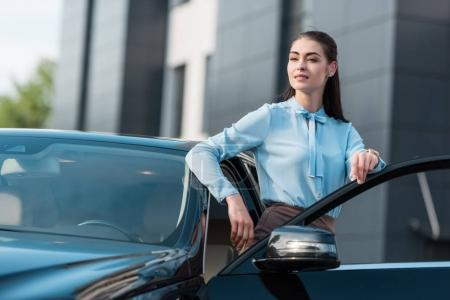 businesswoman leaning on car