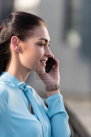 Photo pour Vue latérale prise de vue de jeune femme souriante parlant sur smartphone - image libre de droit