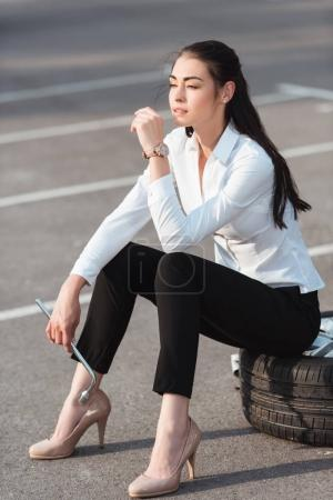 woman sitting on car tire