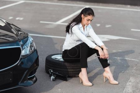 woman sitting on tire with wrench