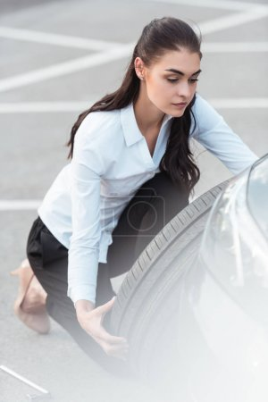 Woman changing car tire