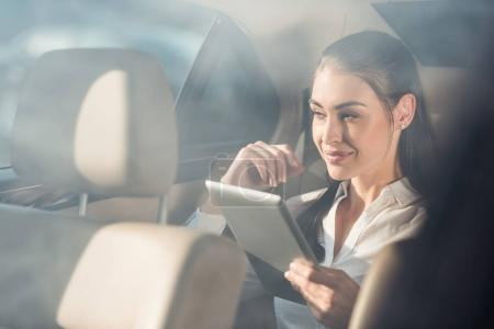 woman in car with digital tablet