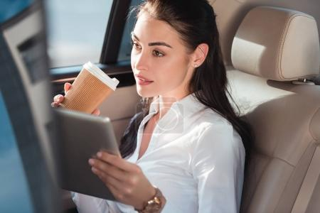 woman in car with digital tablet and coffee