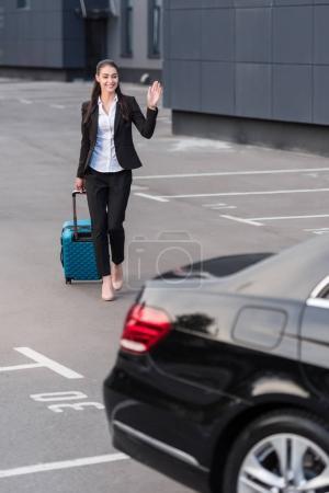 Photo pour Jeune femme en costume de pantalon marchant vers la voiture de tourisme avec valise - image libre de droit