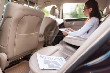 Business newspaper in backseat of car