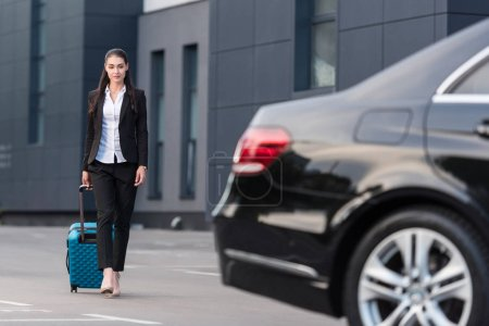 Woman walking with suitcase in parking lot