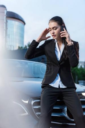 Troubled businesswoman talking on phone