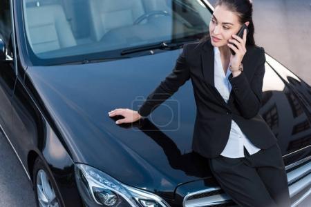 Woman on car talking on phone