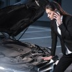 Постер, плакат: woman looking under hood of car