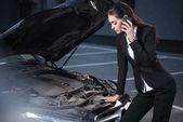 woman looking under hood of car