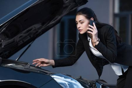 Woman looking under hood of car